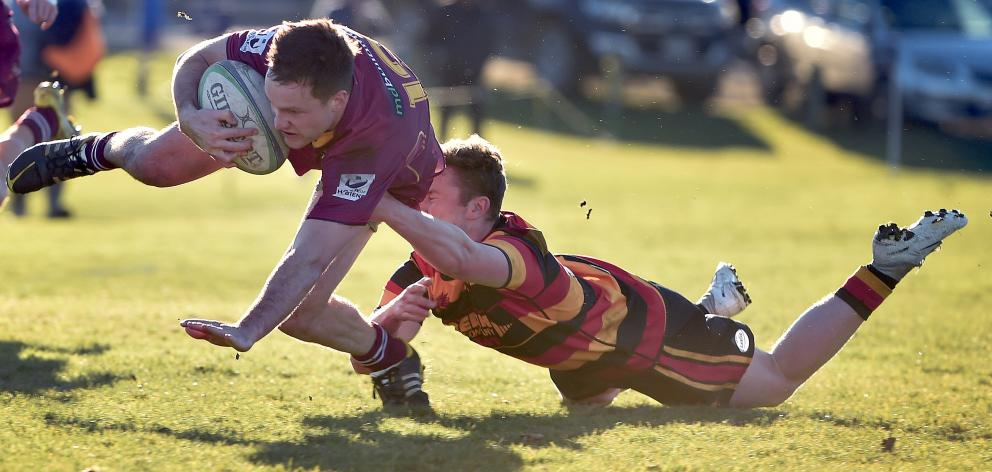 Alhambra Union centre Brad Morgan is tackled by Zingari fullback Devin Redfern during the premier...