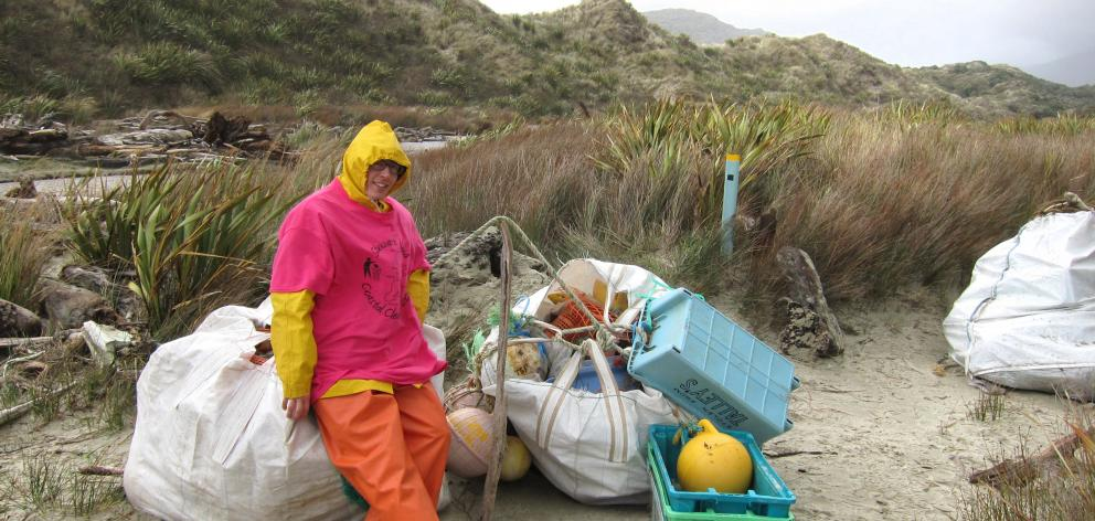 Boi Rickertsen, of Invercargill, sits on bags of rubbish collected on the beaches of Stewart Island.