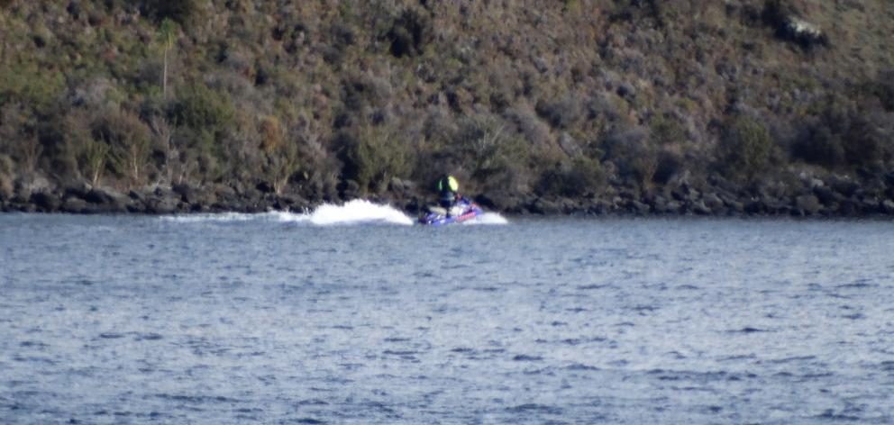 A jet ski helps conduct the search for the missing helicopter and pilot on Lake Wanaka. Photo: Sean Nugent