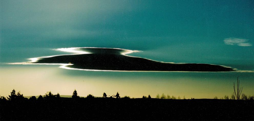 Looking every inch like a swan in flight, this incredible lenticular cloud looming large was...