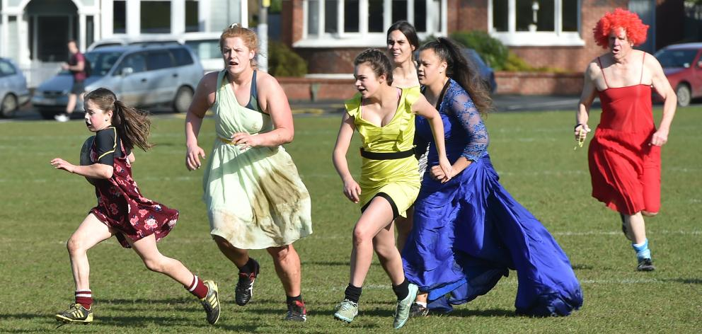 Elisabeth Hutton-Neill (11) is chased by fellow Alhambra Union Rugby Football Club members (from...