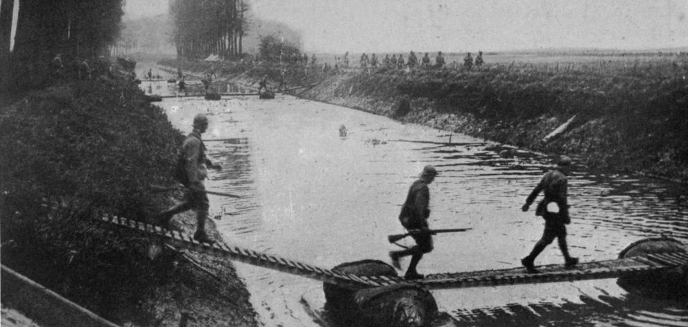 French troops crossing the Anizy canal on a pontoon bridge under fire. — Otago Witness, 21.8.1918.