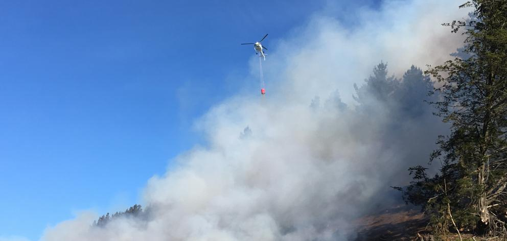 Helicopters carrying  monsoon buckets fight a large fire in an area of harvested forestry at...