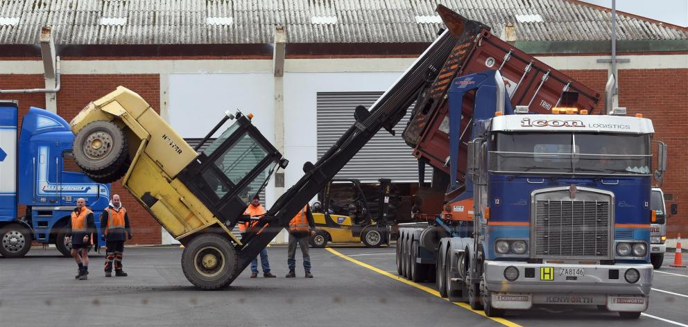 Workers consider what to do next after a forklift tipped forward while lifting a container in a...