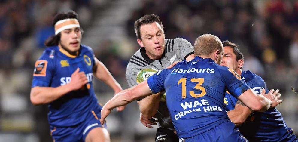 All Black fullback Ben Smith looks to burst through the tackle of Otago centre Matt Faddes as...