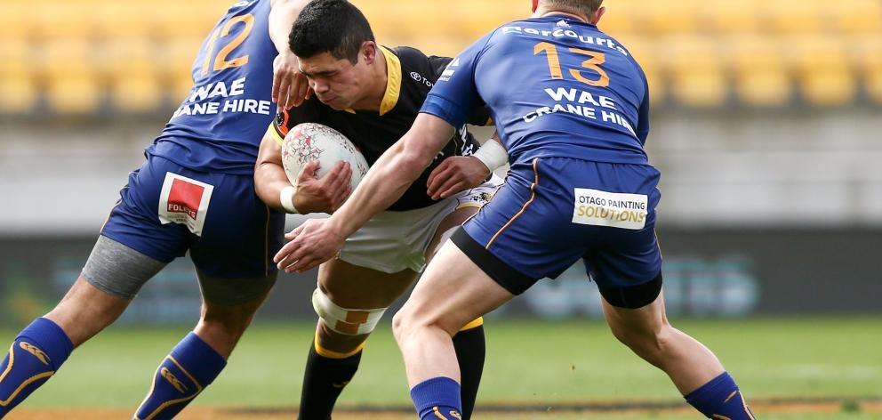 Wellington flanker Du'Plessis Kirifi is tackled by Tomkinson (left) and centre Matt Faddes during...