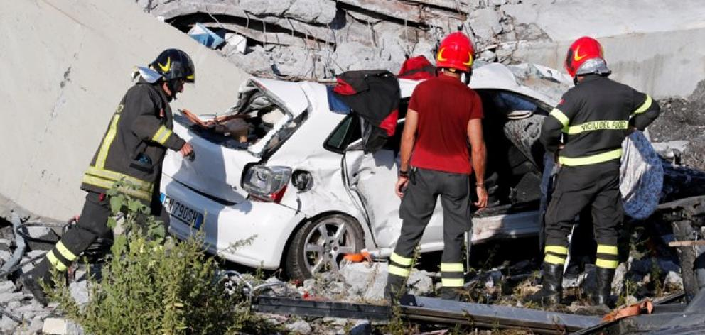 Firefighters stand inspect crushed car at collapsed Morandi Bridge site in Genoa. Photo: Reuters