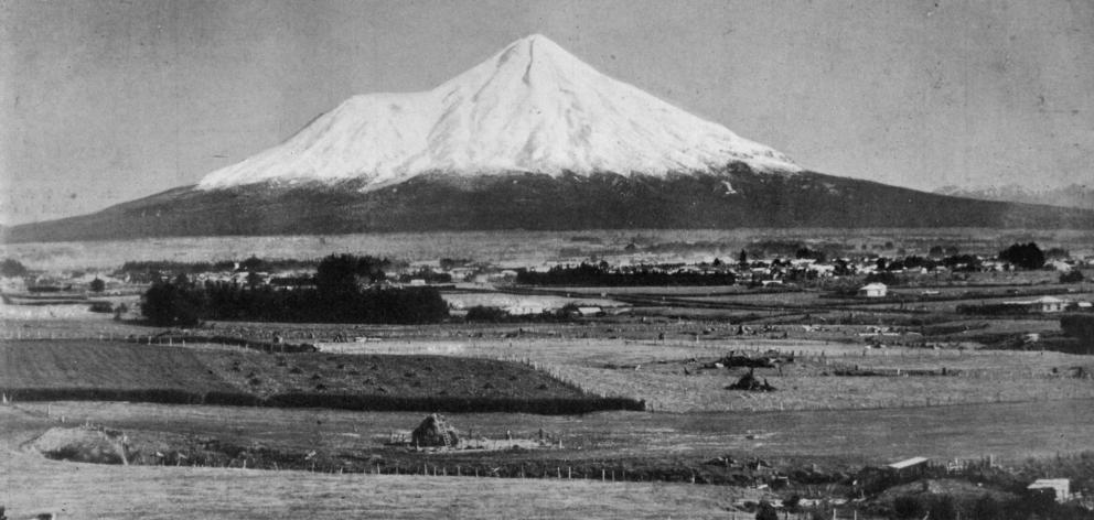 Mount Egmont, Taranaki, with the town of Stratford in the middle distance, after a heavy snowfall...