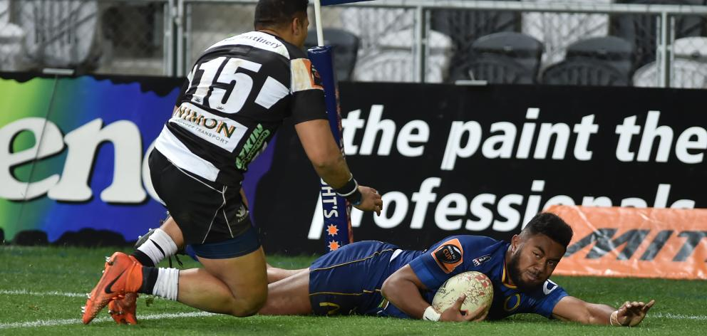 Otago fullback Vilimoni Koroi scores in the corner as his Hawke's Bay counterpart, Jamie Jerry...
