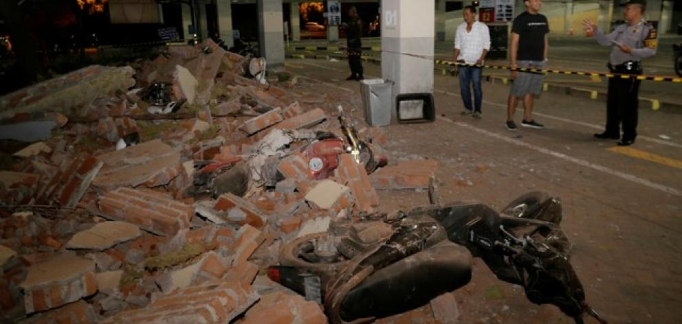 A policeman examines debris that fell and crushed parked motorbikes following a strong earthquake on nearby Lombok island. Photo: Reuters