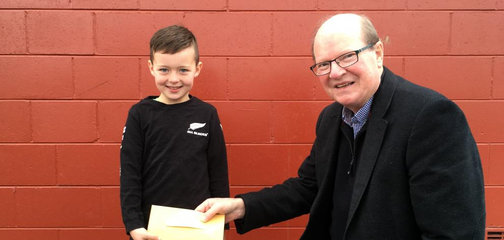 Mason Dunphy gives Taieri Facilities Community Trust member Bill Feather $280 on Tuesday to help build a new aquatic facility in Mosgiel. Photo: Shawn McAvinue
