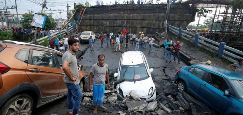 Cars were seen among the rubble and a large portion of the bridge was destroyed. Photo: Reuters