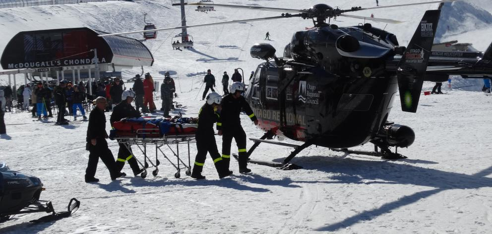 "An injured woman believed to have crashed while ""speed riding'' is carried to the Otago Regional Rescue Helicopter at Cardrona Alpine Resort yesterday. Photo: Sean Nugent"