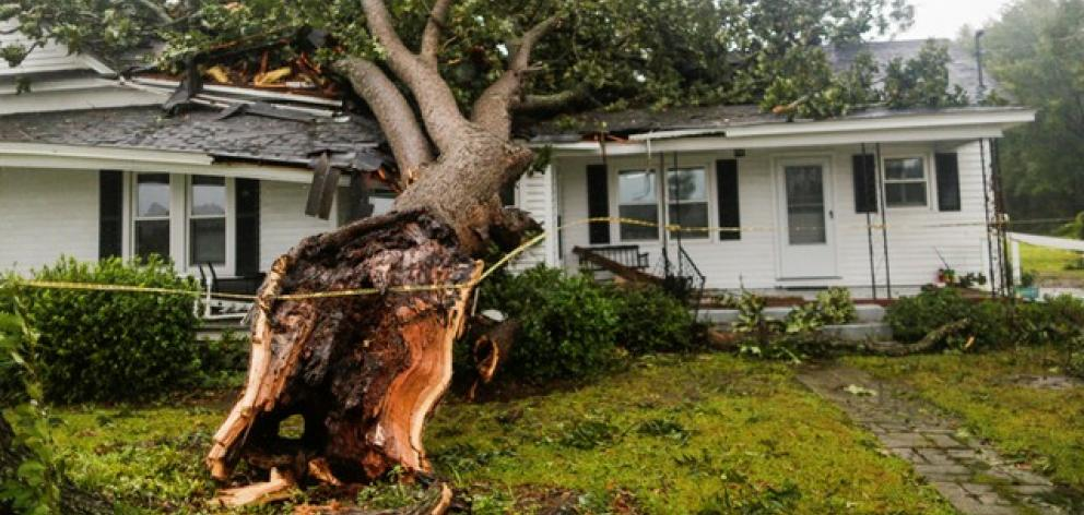 A downed tree rests on a house during the passing of Hurricane Florence in the town of Wilson. Photo: Reuters