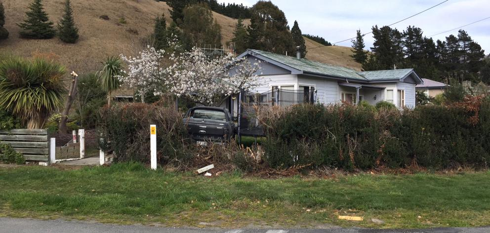 A vehicle sits on a Kurow property after it smashed through a hedge and hit a cherry tree, and narrowly avoided ploughing into a nearby house, after its driver lost control on Sunday morning. Photo: Supplied/NZ Police