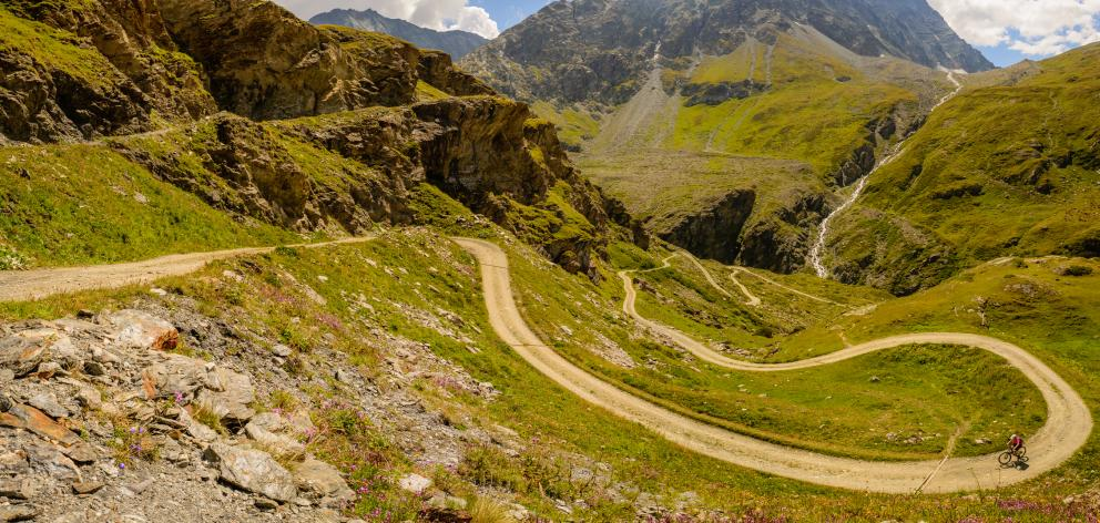 A female mountain biker cycling up a winding path in the Alps. Photo: Getty Images