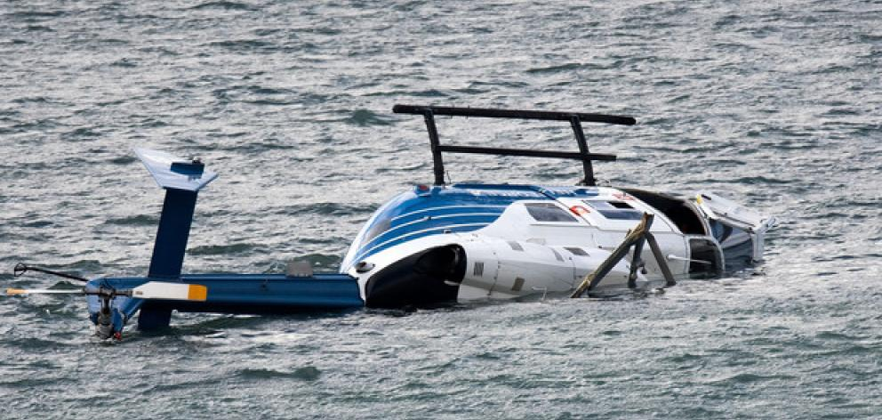 Pilot Rick Lucas clambered uninjured from the chopper after it crashed into Porirua Harbour in May last year (2017). Photo: NZ Herald