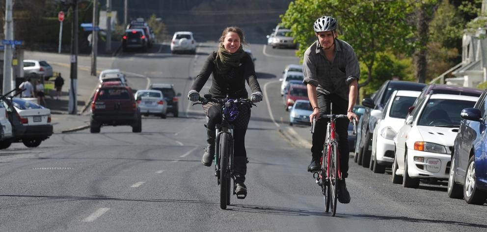 Critical Mass Dunedin participants Kitty Cresswell Riol and Geoff Wigley ride on Dundas St. PHOTO...