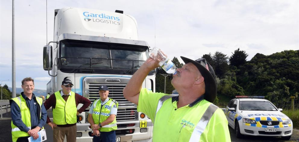 Truck driver Graham Veitch enjoys water provided by NZ Transport Agency transport officer Greg Sims (left), Road Transport Association Otago and Southland area executive Alan Cooper and Sergeant Andrew Savage in Saddle Hill yesterday. Photo: Stephen Jaqui