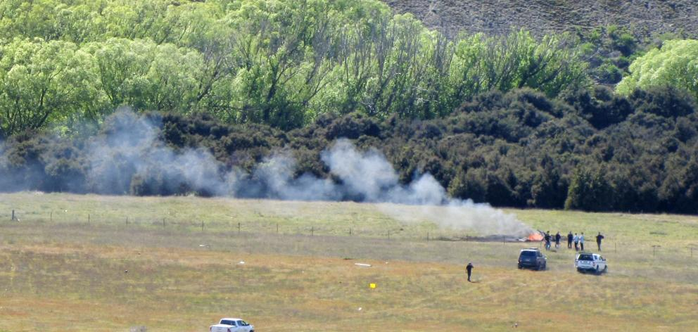 Smoke rises from the wreck of a helicopter crash near Wanaka Airport earlier today. Photo: Mark Price