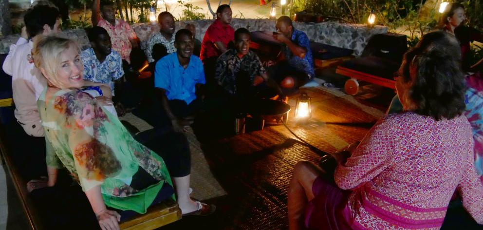 Guests and staff mingle at a kava ceremony at Tropica Island Resort, Fiji.
