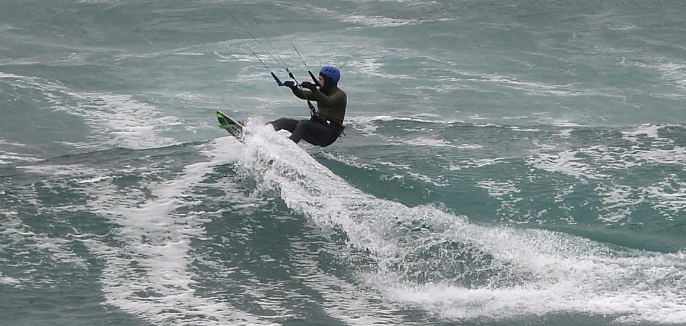 A kite surfer rides through the waves brought in by a southerly front just off St Kilda beach in...