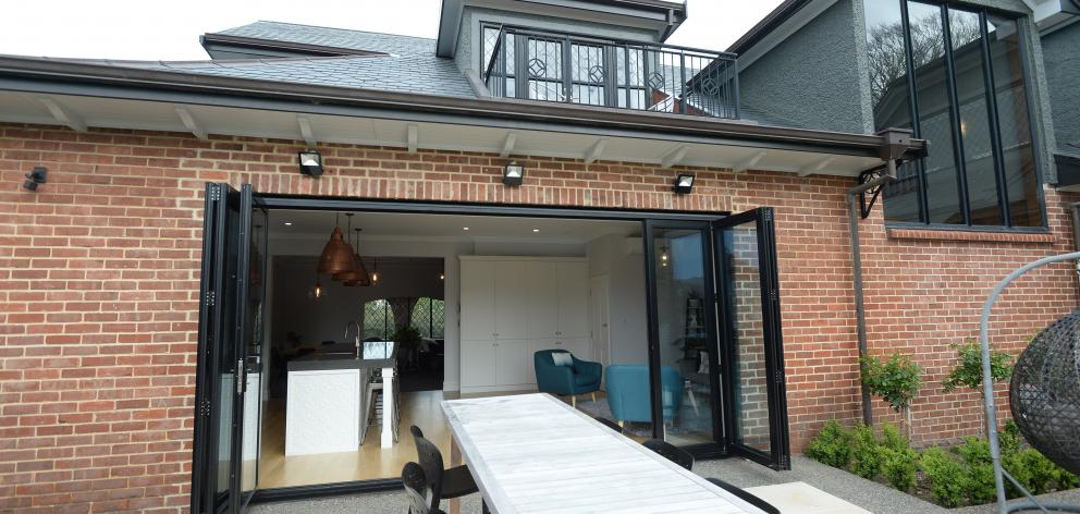 Large bifold doors open the kitchen-family area to a patio designed by Wayne Butson of Design and...