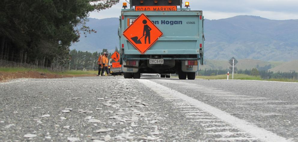 A grader chips off the rumble strip from the edge of State Highway 8A between Tarras and Luggate...