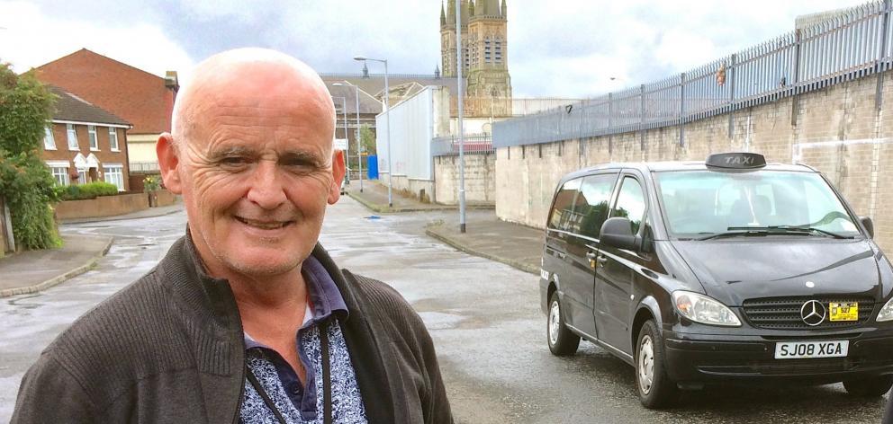 Black Taxi Tours司机Jim O'Neill在贝尔法斯特Falls Rd附近。