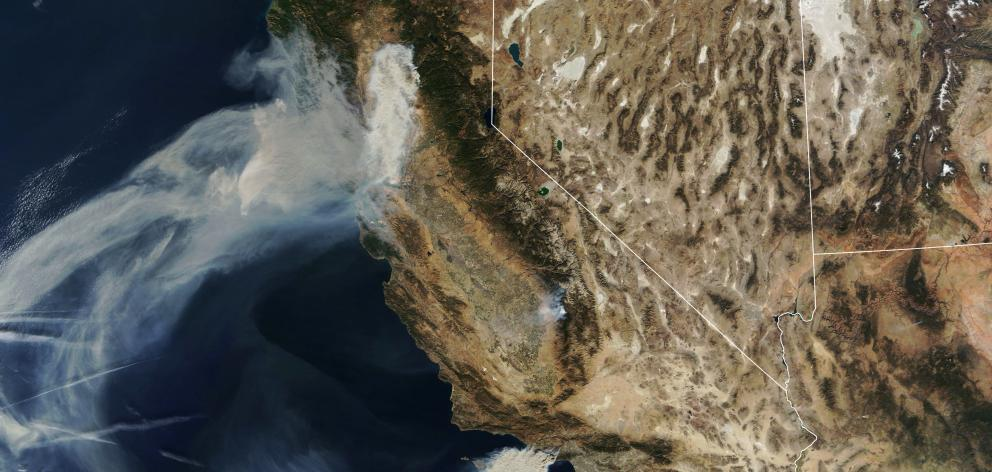 Satellite image shows smoke continuing to spread west from the Camp Fire and two more fires, the Hill and Woolsey Fires in southern California. Photo: Nasa via Reuters.