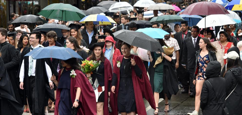 University of Otago graduands surge along George St, Dunedin, on Saturday morning in the first of...