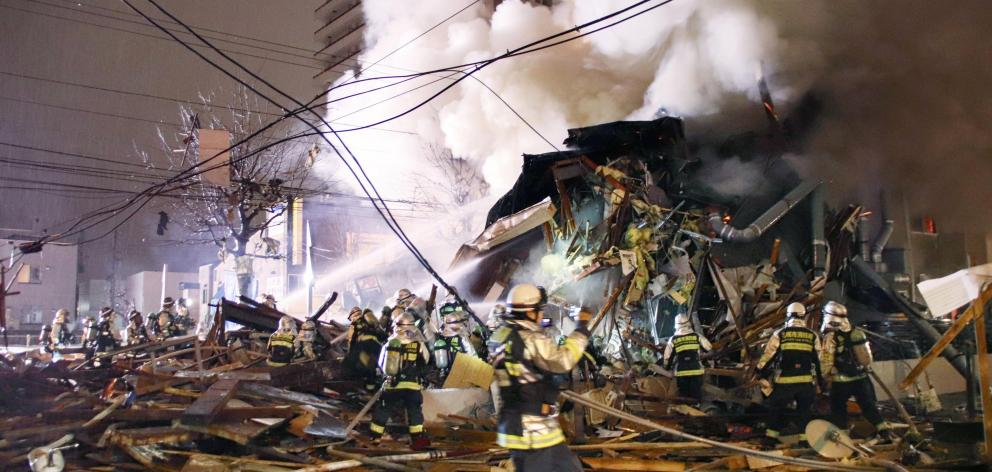 Firefighters operate at the site where a large explosion occurred at a restaurant in Sapporo. Photo: Kyodo via Reuters
