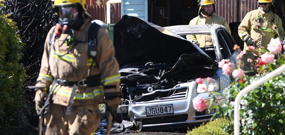Firefighters inspect the wreckage of a car  in Mosgiel which burst into flames yesterday morning....