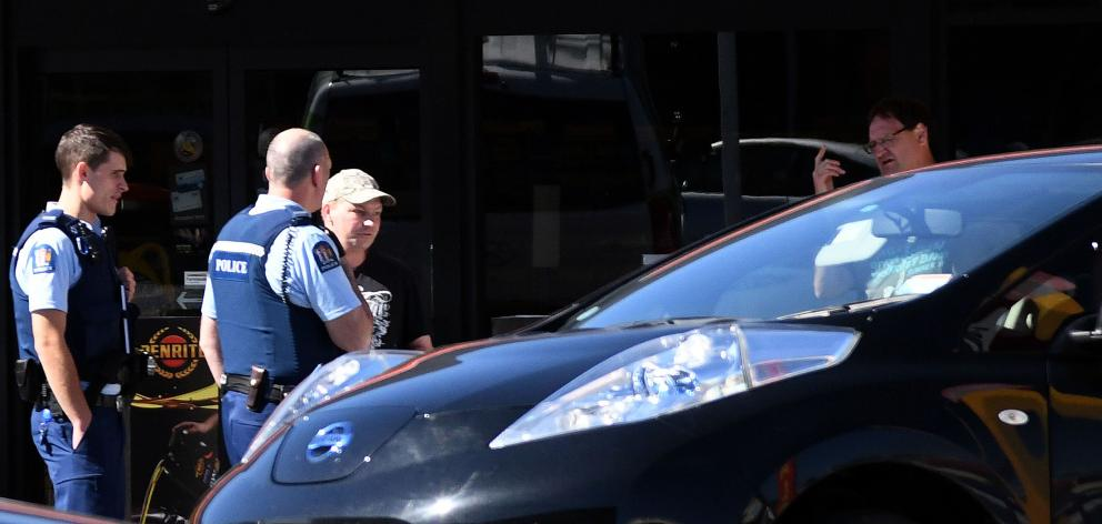 Police interview the alleged victim (left) and a witness  in the Repco car park in Dunedin...