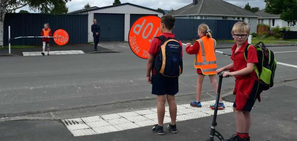 Silverstream School pupil Luke McHale (8) prepares to cross Green St in Mosgiel on his scooter with pupil Beau French (11) under the guidance of pupils and road patrollers Sarah Evans (left), Hannah Bray (both 10) and principal Greg Hurley. Photo: Shawn M