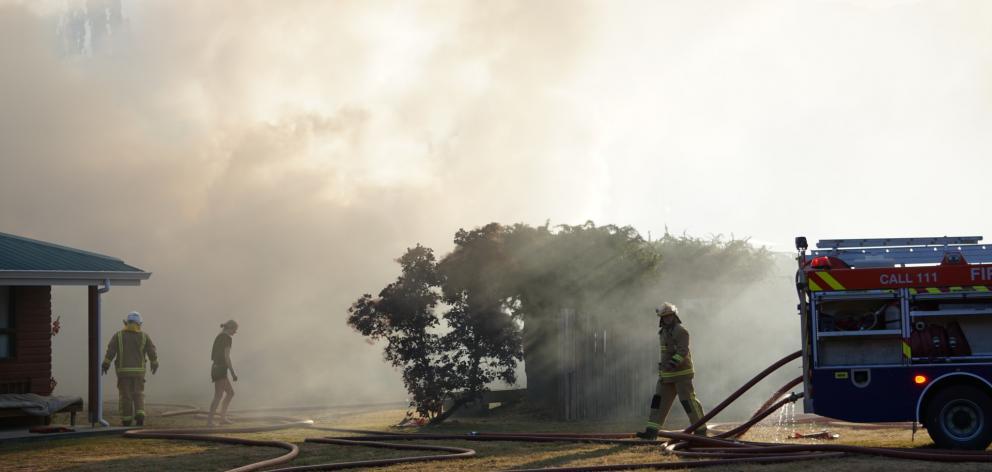 Firefighters battled a roaring garage fire in Albert Town last night. Photos: Sean Nugent