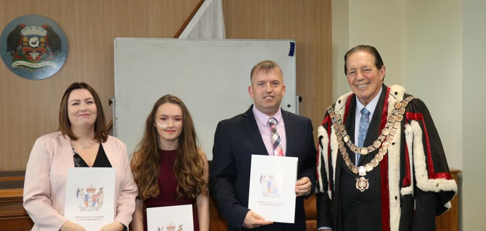 Invercargill Mayor Tim Shadbolt presents the McManus family, (from left) Billie-Jean, Jodie and Colin, with their citizenship certificates in July this year. A record number of people in Invercargill became citizens in 2018. Photo: Supplied