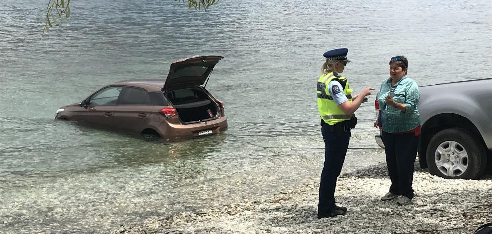 Police, and curious onlookers went to the lakefront across the road from the Rydges Hotel after the car rolled into the lake. Photo: Daisy Hudson
