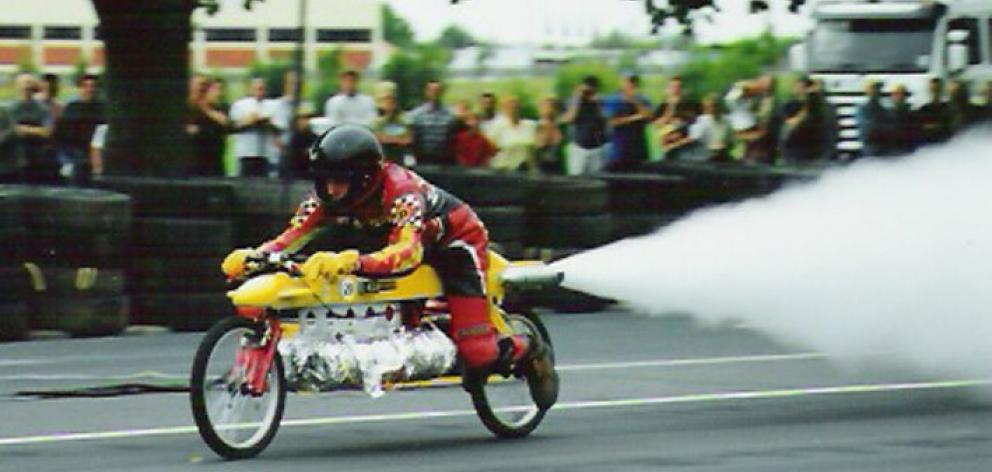 Peter Beck shoots down Princes St, Dunedin, on his rocket-powered bicycle.