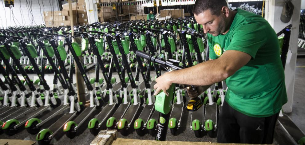 Mechanic Vlatko Jovanovski repairs Lime scooters in storage at Lime's warehouse in Kingsland,...