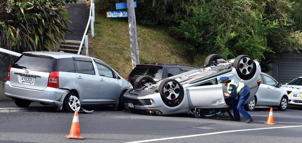 A police officer inspects a car on its roof on Kenmure Rd in Dunedin yesterday. PHOTO: PETER...