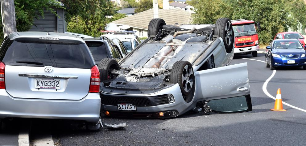 Dunedin police stop traffic on Kenmure Rd after a stolen car crashed and rolled on Sunday. PHOTO:...