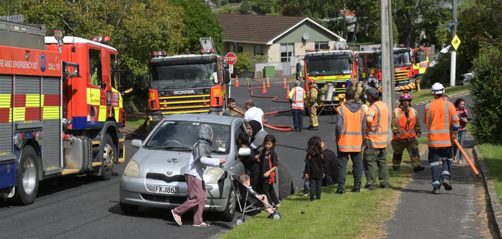 Members of Dunedin's Syrian community watch as firefighters battle a fire, yesterday afternoon, in a house which is home to former refugee Mohammad Saad Aldeen and his family. Photo: Linda Robertson