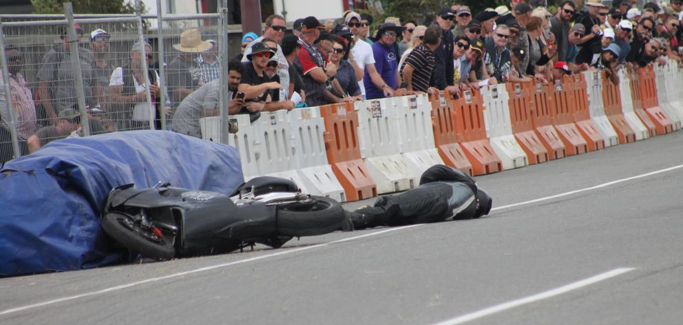 Motorcyclist Tony Campbell, of New Plymouth, lies on the track after crashing his Aprilia RSV...