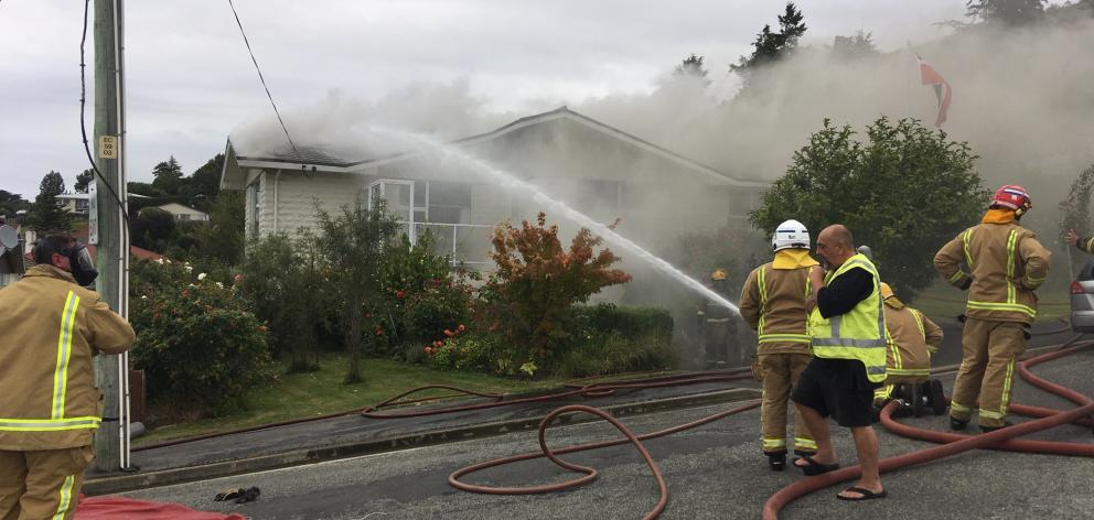 Firefighters use a hose to douse the blaze at a property in Oamaru this evening. Photo: Daniel Birchfield
