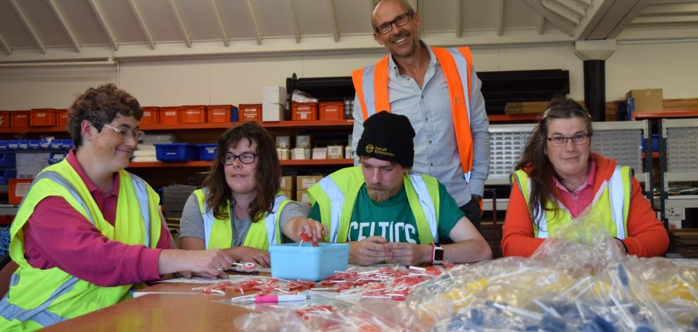 Cargill Enterprises chief executive Geoff Kemp (standing) watches as production workers (from left) Geraldine Fowler, Tegan Howard, Cliff Pope and Yvonne McClintock put stickers on lollipops in South Dunedin last week. Photo: Shawn McAvinue