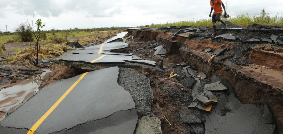 A man passes through a section of the road damaged by Cyclone Idai in Nhamatanda about 50 kilometres from Beira, in Mozambique. Photo: AP