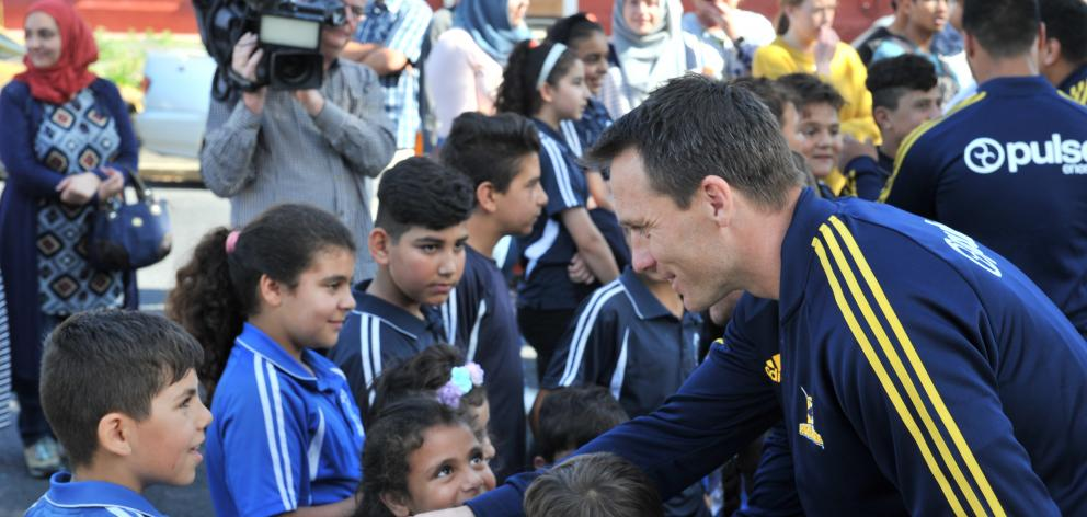 Ben Smith shakes a boy's hand as he arrives with the Highlanders at the Al Huda mosque in Dunedin today. Photo: Christine O'Connor