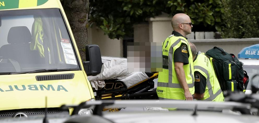 Ambulance staff take a man from outside a mosque in central Christchurch. Photo: AP