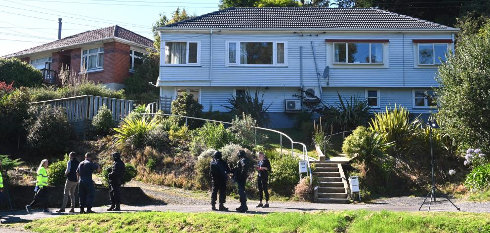 Police armed offenders personnel search the property in Somerville St, Dunedin, on Saturday....